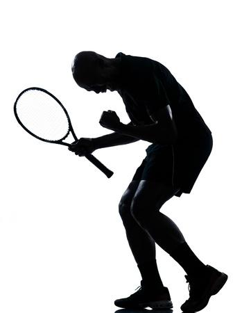 jugando tenis: el hombre africano afro americano jugador de jugar al tenis hombre tenista sucess feliz victoria gritando en el estudio aislado en fondo blanco Foto de archivo