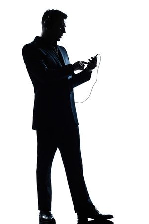 one caucasian man text messaging telephone listening to music full length silhouette in studio isolated white background photo