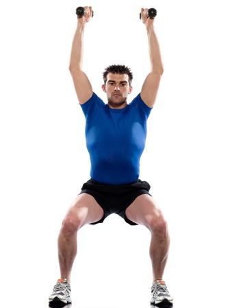 squat: man doing workout squats weight training crouching on studio white isolated background