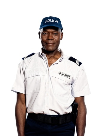 Portrait of an afro American mature police officer standing in studio on white isolated background photo