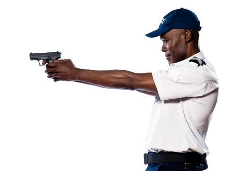 vigilance: Side view of an afro American police officer aiming gun in studio on white isolated background
