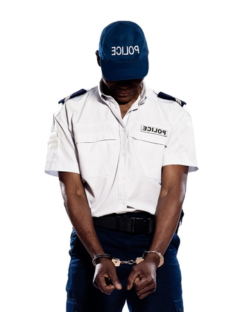 Hand cuffed police officer with head down standing on white isolated background photo