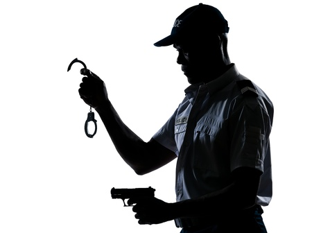 An afro American policeman holding handcuffs and handgun in studio on white isolated background photo