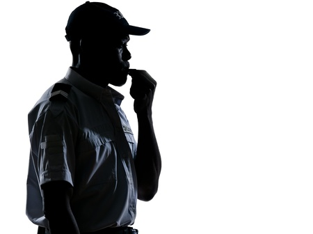 traffic police: Side view of an afro American policeman blowing whistle in studio on white isolated background