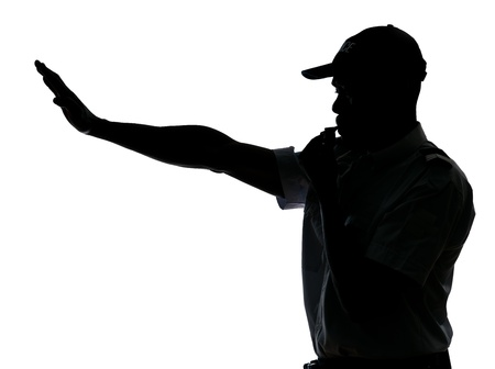 An afro American traffic cop making stop gesture while blowing whistle in studio on white isolated background photo