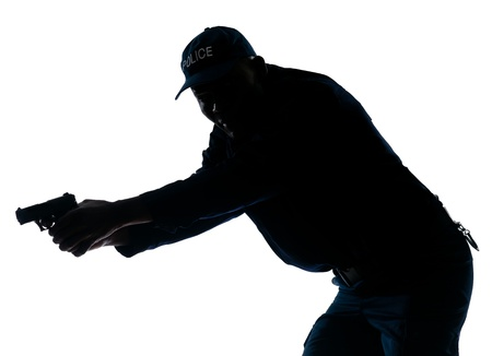 An afro American policeman holding handgun in studio on white isolated background photo