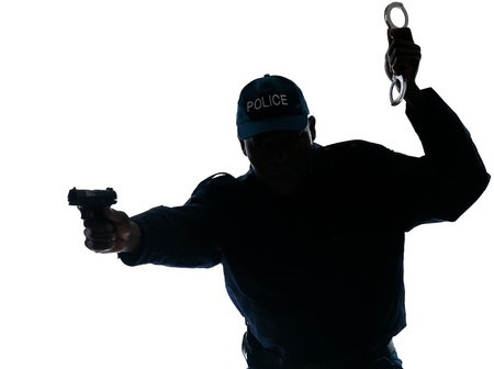 Silhouetted Afro American policeman aiming handgun while holding handcuffs isolated on white background photo