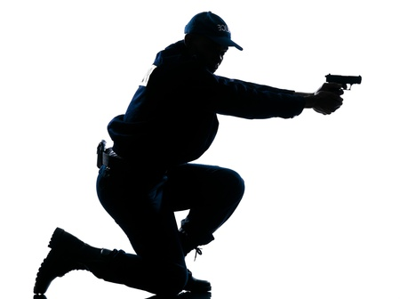Side view of a silhouetted Afro American police officer aiming gun isolated on white background photo