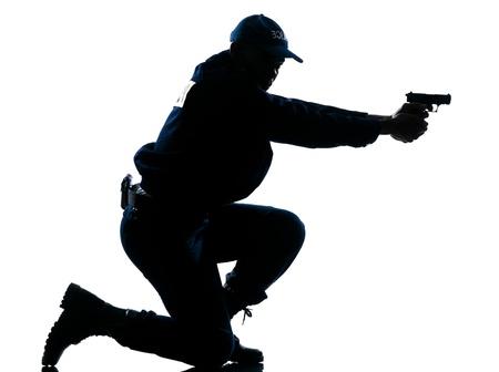 hombre disparando: Vista lateral de una silueta de oficial de la policía afro americano con el objetivo pistola sobre fondo blanco Foto de archivo