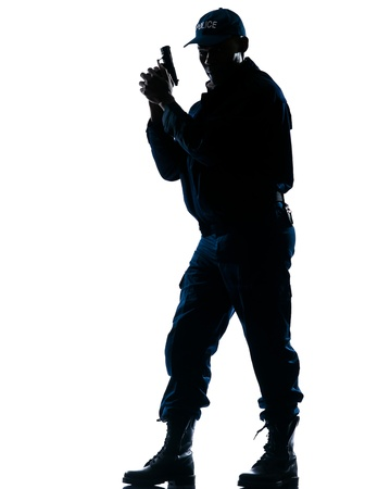 security laws: Full length of an alert afro American policeman standing with handgun on white isolated background Stock Photo