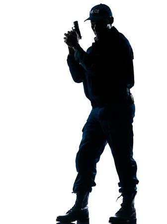 gorra polic�a: Longitud total de una alerta por polic�a afro-americana de pie con arma de fuego en el fondo aislado blanco Foto de archivo
