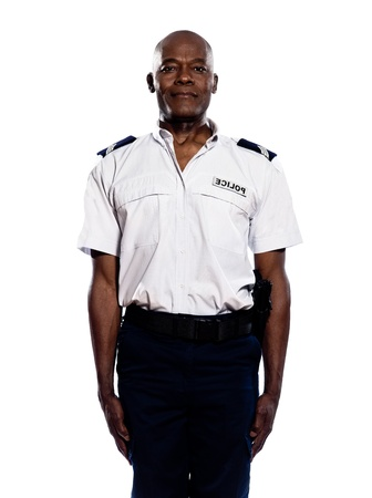 Portrait of a smart afro American police officer in uniform standing in studio on white isolated background photo