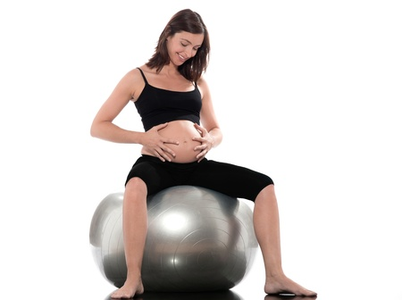 pregnant caucasian woman sitting on swiss ball isolated studio on white background photo