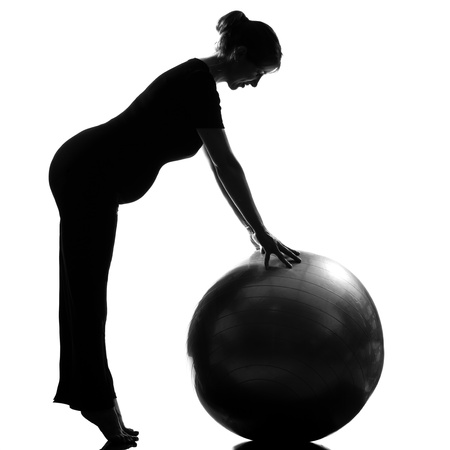 isolated on the white background: beautiful caucasian pregnant woman exercising fitness workut pilates with fitness ball in full length silhouette on studio isolated white background