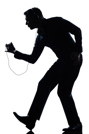one caucasian man dancing happy listening to music full length silhouette in studio isolated white background photo