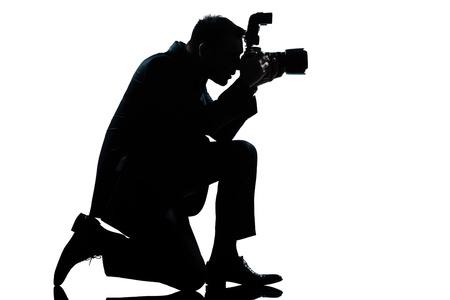 arrodillarse: un hombre cauc�sico de rodillas silueta fot�grafo de larga duraci�n en el estudio aislado sobre fondo blanco Foto de archivo