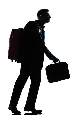one caucasian business traveler man walking with suitcase on shoulders full length silhouette in studio isolated white background photo