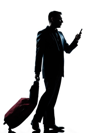 business traveler: one caucasian business traveler man walking with telephone and  suitcase  full length silhouette in studio isolated white background