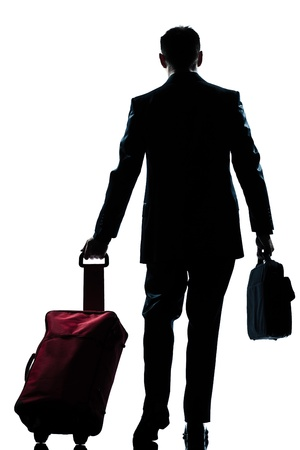 rear view one caucasian business traveler man walking with suitcase  full length silhouette in studio isolated white background photo