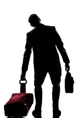rear view one caucasian business traveler man tired with suitcase  full length silhouette in studio isolated white background photo