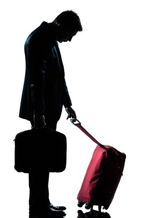profile one caucasian business traveler man tired with suitcase  full length silhouette in studio isolated white background photo