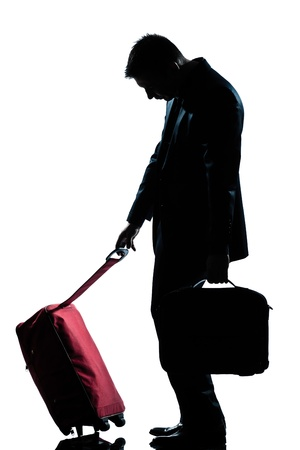 side view one caucasian business traveler man tired with suitcase  full length silhouette in studio isolated white background photo