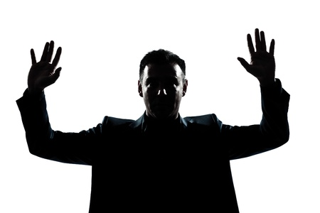 surrender: one caucasian man portrait silhouette hands up in studio isolated white background