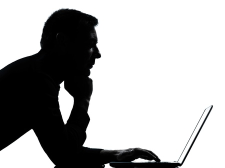 typing man: one caucasian business man computing computer laptop serious portrait silhouette in studio isolated on white background