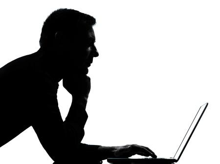 mecanograf�a: un hombre de negocios caucasian equipo de computaci�n port�til silueta retrato serio en el estudio aislado sobre fondo blanco