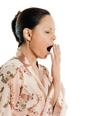 Side view of Asian sleepy woman yawning in studio isolated on white background
