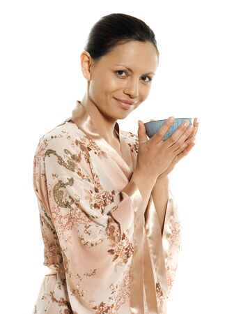 Portrait of beautiful Asian woman drinking tea in studio isolated on white background photo