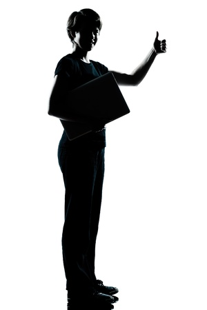 one caucasian young teenager silhouette boy  girl holding carrying laptop computer thumb up full length in studio cut out isolated on white background photo