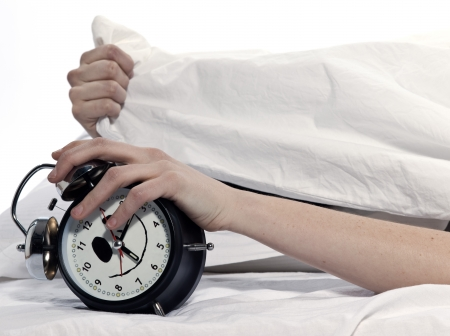 young woman woman in bed awakening tired holding alarm clock on white background photo