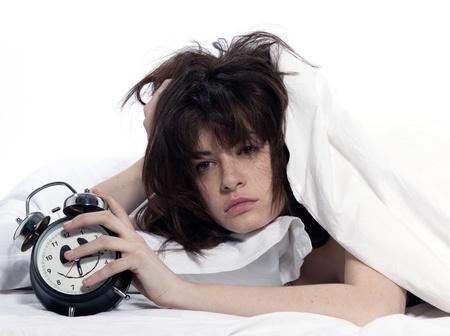 insomnio: mujer joven en el despertar de la cama cansado reloj celebración de alarma en el fondo blanco Foto de archivo
