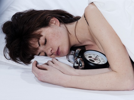 young woman in a white sheet bed on white background sleeping with her alarm clock photo