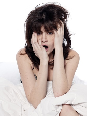 one young caucasian woman awakening yawning tired insomnia in a white sheet bed on studio isolated  white background photo