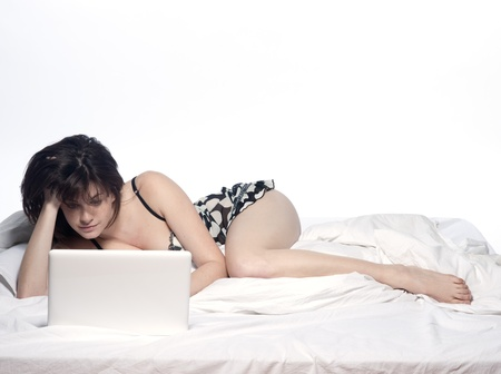 young woman in a white sheet bed on white background with a pc computer laptop photo