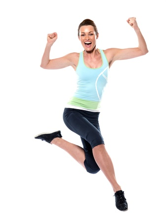 people exercising: woman running sportswear happy jumping on studio white isolated background