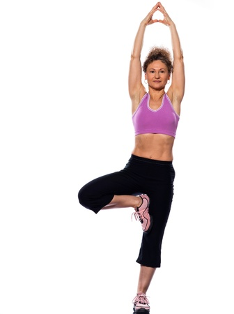 beautiful mature woman yoga tree pose on isolated white background doing stretching exercise photo