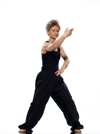 fifty: mature woman praticing tai chi chuan in studio on isolated white background