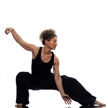 lunges: mature woman praticing tai chi chuan in studio on isolated white background