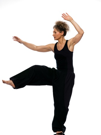chi: mature woman praticing tai chi chuan in studio on isolated white background
