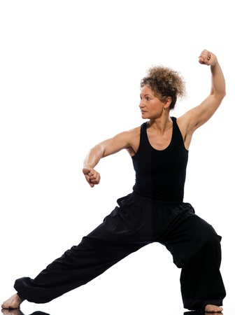 one senior adult woman: mature woman praticing tai chi chuan in studio on isolated white background