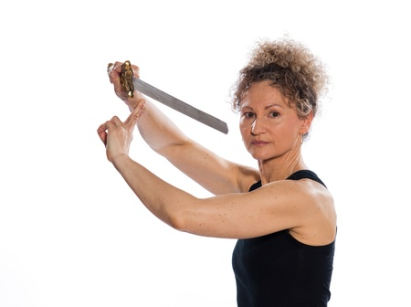 40 50: mature woman praticing tai chi chuan with sword in studio on isolated white background