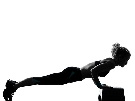one woman exercising workout fitness aerobic exercise abdominals push ups posture on studio isolated white background Stock Photo - 11753103