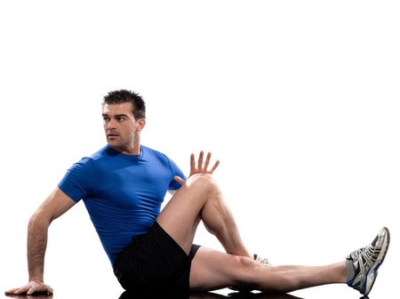 knee bend: man on Abdominals rotation workout posture on white background. Sit up, straighten one leg and bend the other one. Hold the knee and bring it towards you for 10-20 seconds. Release and switch.