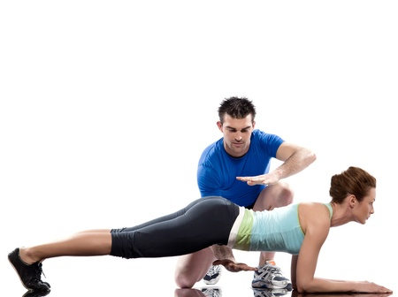 plank position: one caucasian couple man aerobic trainer positioning woman  Workout coach Posture in indoors studio isolated on white background Stock Photo