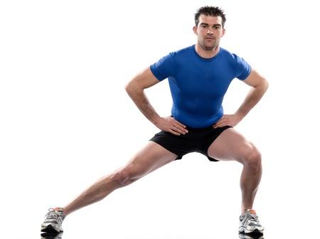 estiramientos: se extiende la postura de entrenamiento por un hombre en estudio de fondo blanco