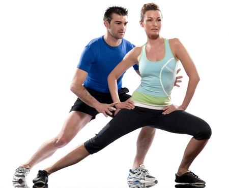 un hombre caucásico entrenador aeróbico posicionamiento mujer de entrenamiento técnico en el estudio de la postura en el interior sobre fondo blanco Foto de archivo