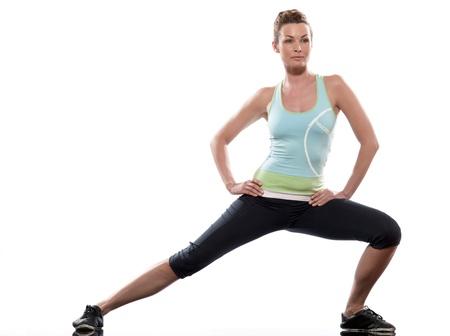 gimnasia aerobica: se extiende la postura de entrenamiento por una mujer en el estudio de fondo blanco Foto de archivo